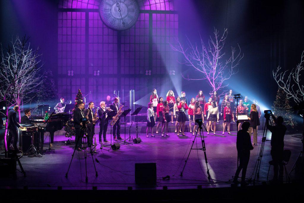 Scena oświetlona niebiesko-fioletowym światłem. Na środku stoi chór dziecięcy ubrany w swetry z motywami świątecznymi. Przed nimi stoi kierownik chóru. Po lewej stronie stoi czterech mężczyzn. Trzech gra na saksofonach, jeden na trąbce. Z przodu dwie osoby przy statywach z aparatami.