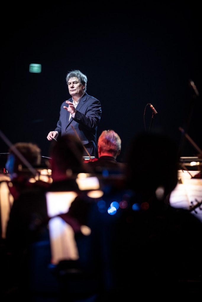 Dyrygent trzymający batutę, stoi z uniesioną ręką przed orkiestrą.