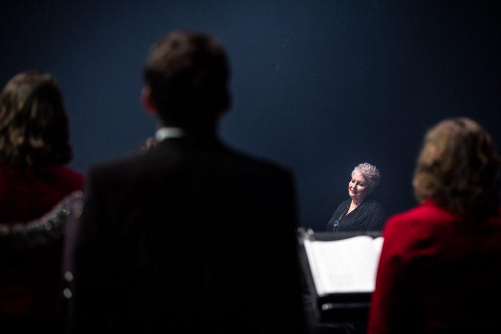 Na zdjęciu stoi kilka osób stojących tyłem. Dalej stoi kierownik chóru Prof. Violetta Bielecka.