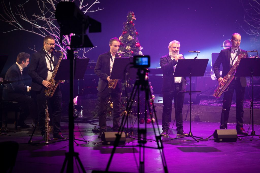 Czterech mężczyzn stoi przed pulpitami do nut. Trzech gra na saksofonach, jeden na trąbce. Za nimi stoi duża choinka. Z przodu widoczne statywy, jeden z aparatem, drugi z lampą.