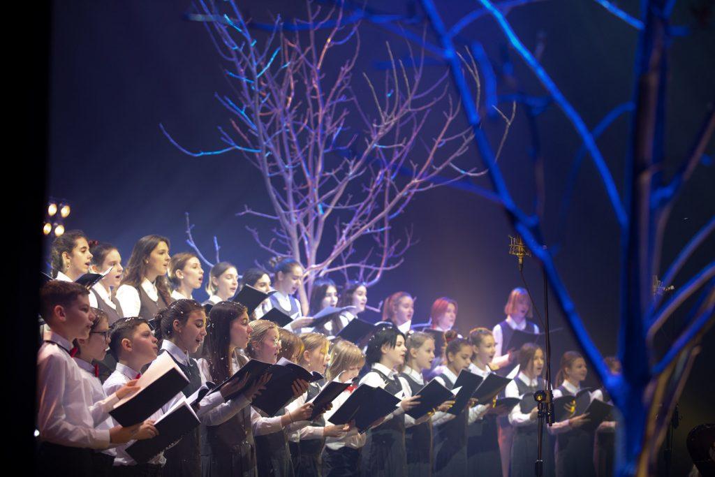 Scena oświetlona na niebiesko. W dwóch rzędach stoi Dziecięcy Chór Opery i Filharmonii Podlaskiej. Wszyscy trzymają rozłożone nuty. Za nimi duże drzewo bez liści.