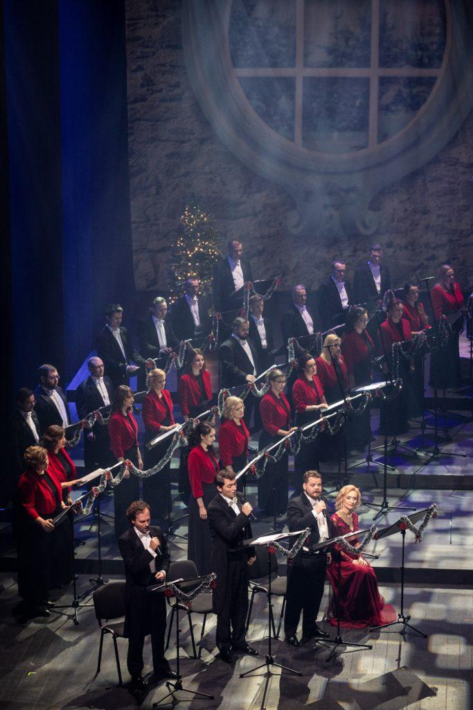 Na zdjęciu po lewej stronie stoi część chóru opery. Z przodu stoi trzech mężczyzn z mikrofonami. Obok na krześle siedzi kobieta w czerwonej sukience.