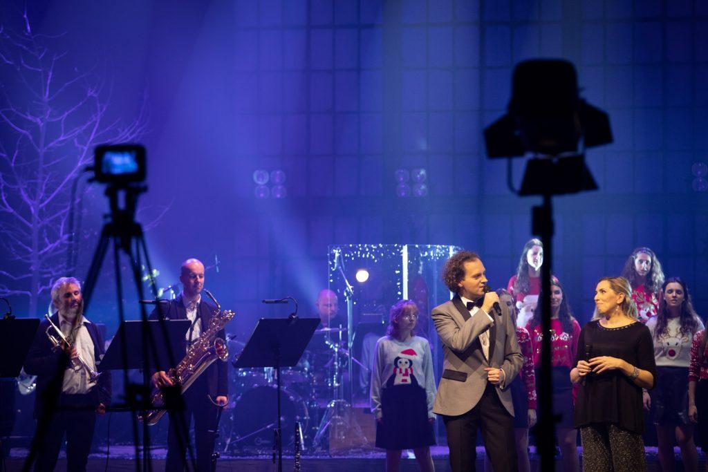 Scena oświetlona niebieskim światłem. Na scenie mężczyzna ubrany elegancko, trzyma mikrofon . obok niego kobieta - kierownik chóru dziecięcego opery. Za nimi, w swetrach z motywami świątecznymi stoi chór dziecięcy opery. Po lewej stronie , przy pulpitach stoi dwóch mężczyzn z instrumentami. W oddali siedzi mężczyzna przy perkusji. Z przodu widoczny statyw z aparatem, obok drugi z lampą.