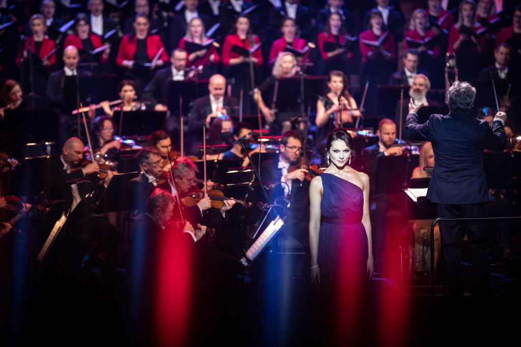 Z przodu stoi kobieta w długiej, eleganckiej sukni. Po prawej stronie, na podeście stoi dyrygent. Z tyłu siedzi orkiestra, a za nią stoi chór opery z otwartymi nutami.