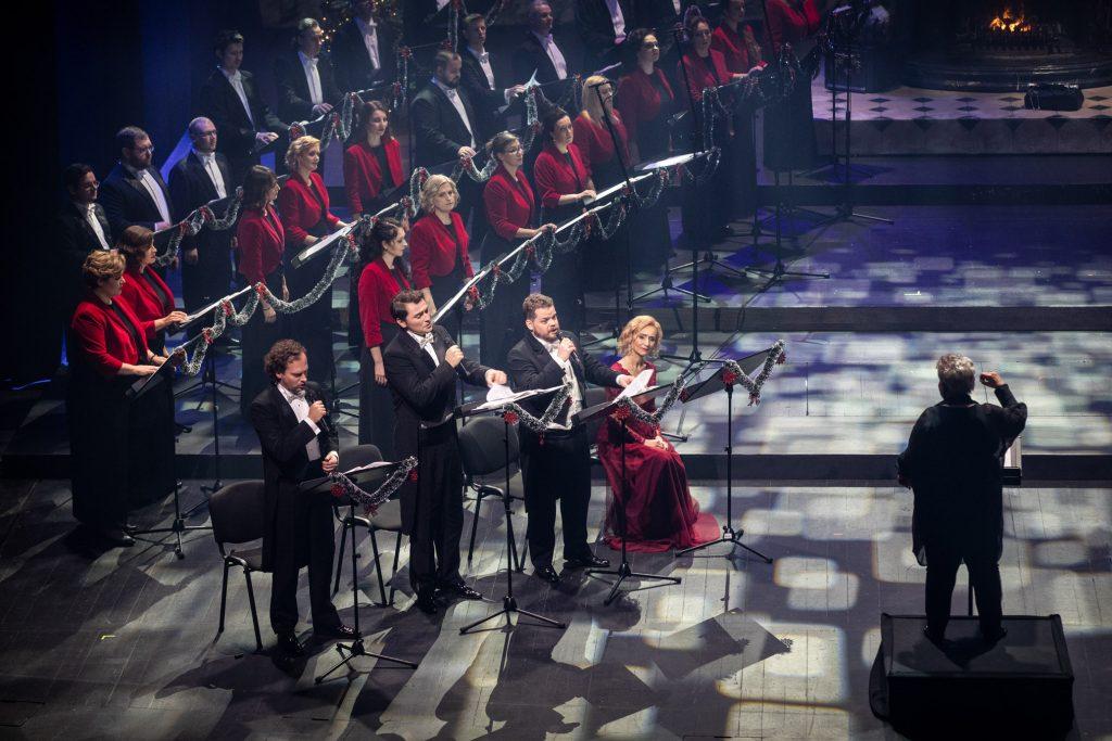 Na zdjęciu po lewej stronie stoi część chóru opery. Z przodu stoi trzech mężczyzn z mikrofonami. Obok na krześle siedzi kobieta w czerwonej sukience. Na środku stoi dyrygent.
