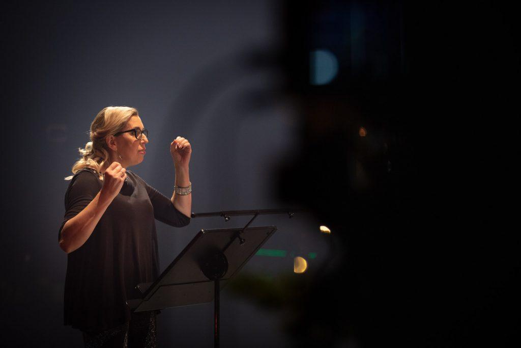 Scena w półmroku. Przy pulpicie kobieta w czarnej bluzce, trzyma ręce lekko uniesione do góry.