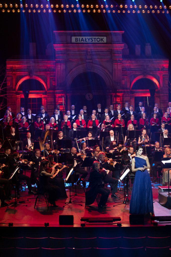 Scena oświetlona czerwonym światłem. Z przodu po prawej stronie stoi solistka w długiej, niebieskiej sukni. Za nią siedzi Orkiestra Opery i Filharmonii Podlaskiej. Z tyłu stoi chór opery trzymający otwarte nuty. Na końcu widoczny jest budynek z dużymi, zaokrąglonymi oknami , z napisem ''Białystok''. Z góry świecą smugi niebieskiego światła.