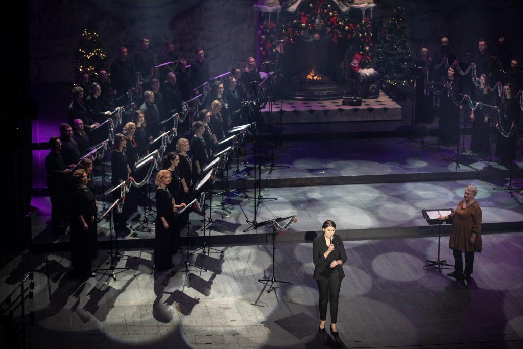 Na scenie po obydwu stronach stoi Chór Opery i Filharmonii Podlaskiej. Z przodu stoi kobieta z mikrofonem. Obok, przy pulpicie z nutami stoi dyrygent - Prof. Violetta Bielecka. Na końcu sceny stoi duży kominek w którym pali się ogień. Dookoła ozdobiony jest bombkami.
