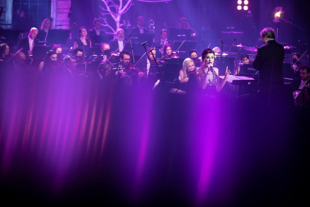 Scena oświetlona fioletowo-niebieskim światłem. Zdjęcie do połowy nieostre. Dalej widać kobietę w błyszczącej sukni, śpiewającej do mikrofonu. Po prawej stronie stoi dyrygent. Za nimi siedzi Orkiestra Opery i Filharmonii Podlaskiej.