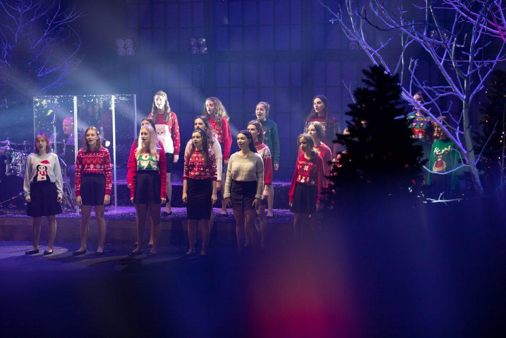 Scena oświetlona na niebiesko. Na niej stoi kilkanaście dziewcząt z chóru dziecięcego w swetrach z motywami świątecznymi. Za nimi siedzi mężczyzna przy perkusji. Po prawej stronie choinka.