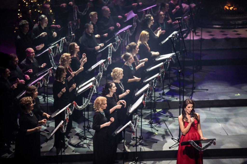 Po lewej stronie chór opery w czarnych strojach. Na środku stoi kobieta z mikrofonem w czerwonej, długiej sukni.
