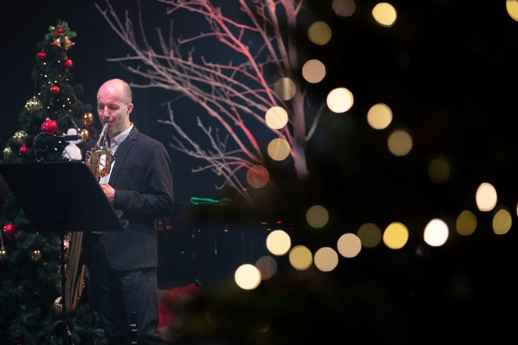 Po lewej stronie mężczyzna gra na saksofonie. Za nim choinka z bombkami. Z tyłu widać gałęzie drzew bez liści.