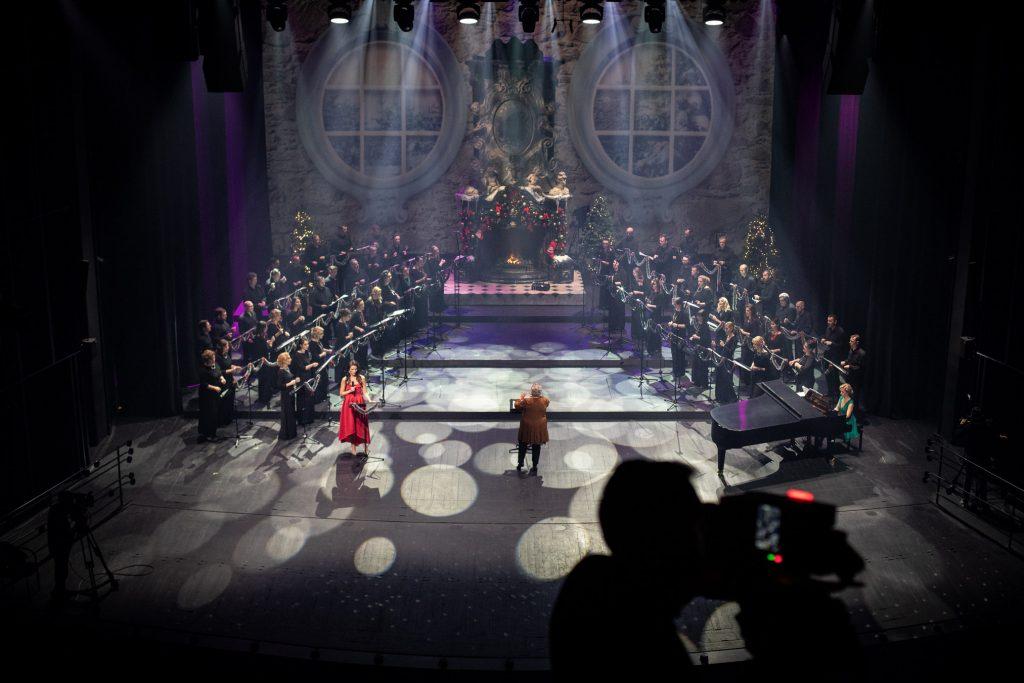 Na scenie po obydwu stronach stoi Chór Opery i Filharmonii Podlaskiej. Na środku przy pulpicie z nutami stoi dyrygent - Prof. Violetta Bielecka. Po lewej stronie stoi kobieta z mikrofonem w czerwonej sukni. Na końcu sceny stoi duży kominek w którym pali się ogień. Dookoła ozdobiony jest bombkami.