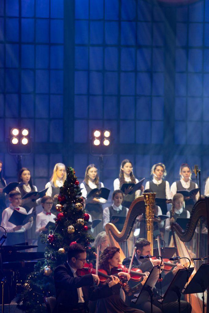 Na zdjęciu z przodu siedzą trzy osoby , grają na skrzypcach. Za nimi stoją dwie harfy. Pomiędzy nimi stoi choinka z bombkami. Z tyłu widać część chóru dziecięcego w galowych strojach.