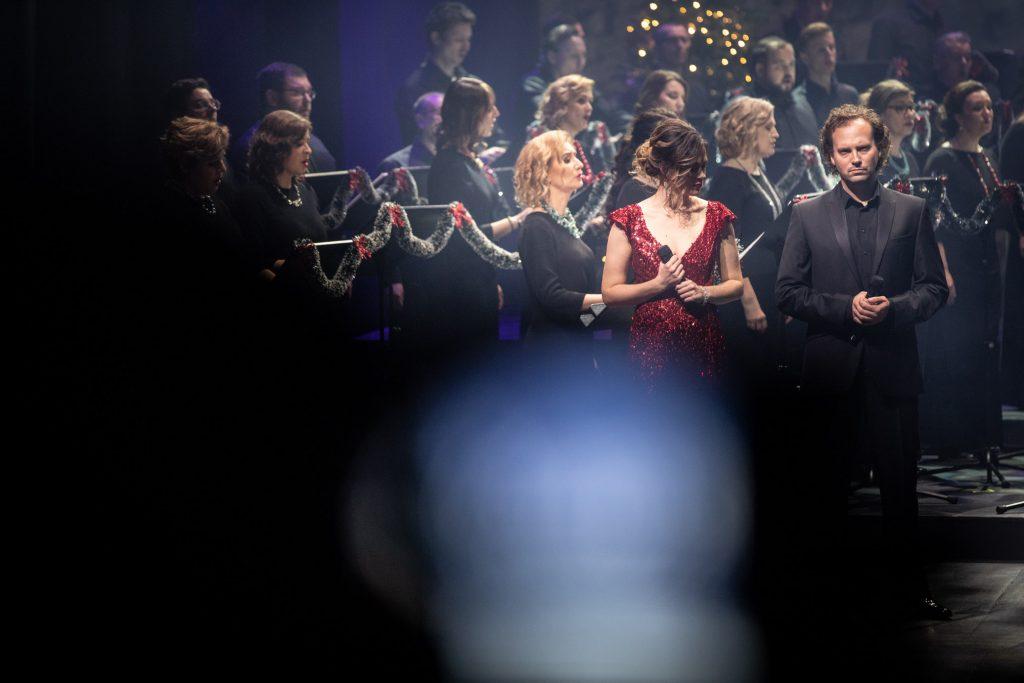 Na środku dwójka solistów z mikrofonami. Kobieta w czerwonej sukni i mężczyzna w czarnym garniturze. Za nimi stoi Chór Opery i Filharmonii Podlaskiej.