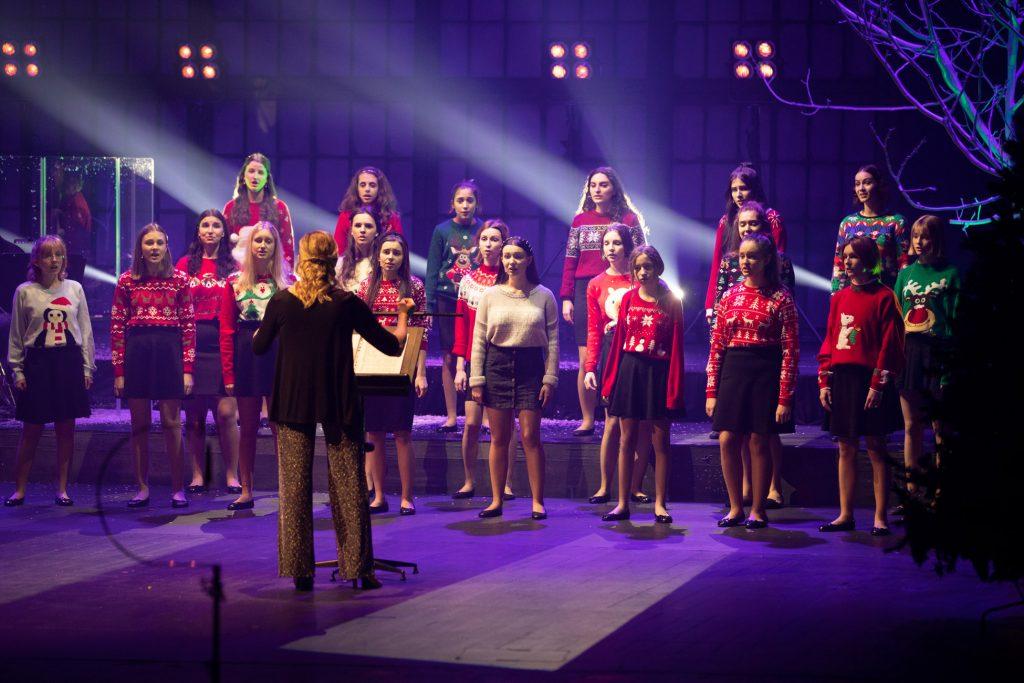 Scena oświetlona niebieskim światłem. Na niej stoi kilkanaście dziewcząt z chóru dziecięcego opery. Wszystkie ubrane w swetry z motywami świątecznymi. Przed nimi, przodem do nich, stoi kobieta w czarnej bluzce - kierownik chóru.