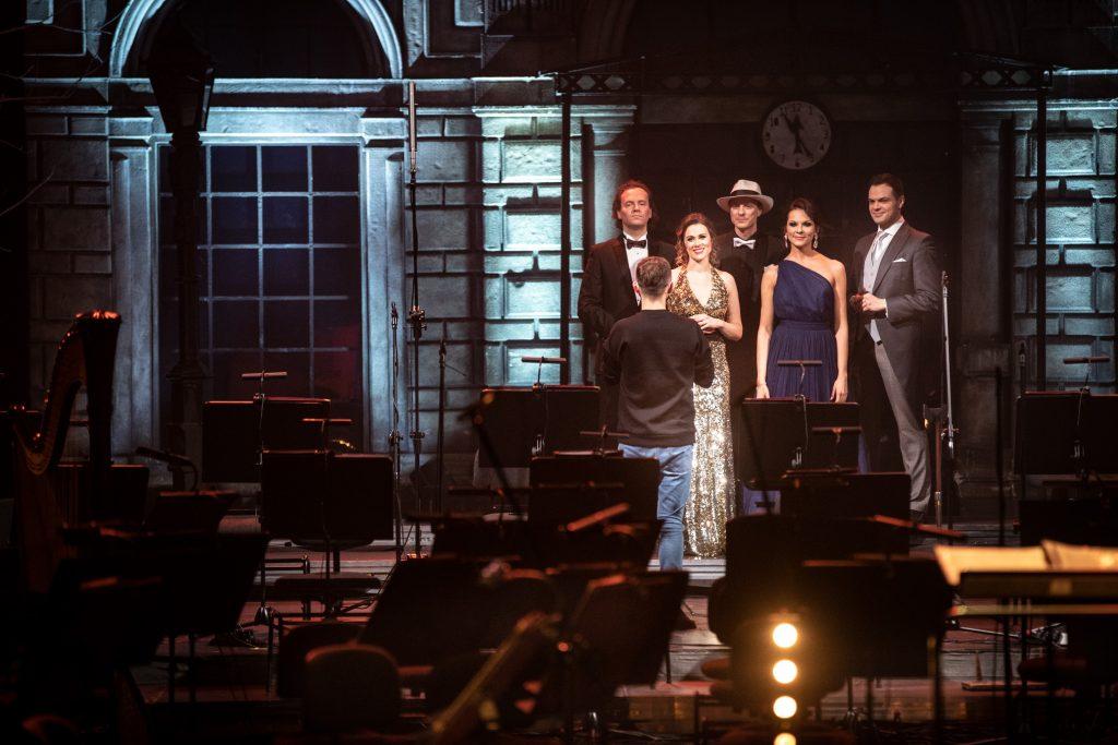 Na końcu sceny stoi obok siebie kilku solistów w galowych kostiumach. Dwie kobiety i trzech mężczyzn. Przed nimi , przodem do nich stoi mężczyzna. Na scenie stoją puste krzesła orkiestry. Obok każdego krzesła stoją pulpity do nut.