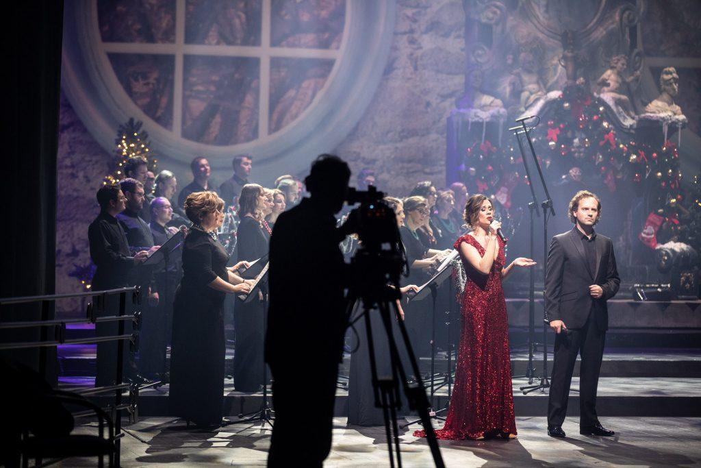 Na środku dwójka solistów z mikrofonami. Kobieta w czerwonej sukni i mężczyzna w czarnym garniturze. Za nimi stoi Chór Opery i Filharmonii Podlaskiej. Z przodu, stoi tyłem mężczyzna przy statywie z kamerą.