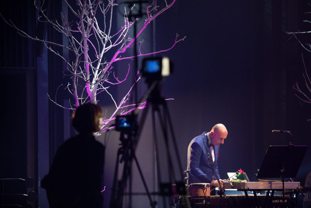Na scenie stoi mężczyzna, gra na dzwonkach. Po lewej stronie stoi kobieta przy statywach z aparatami. Za nią widać szare drzewo bez liści.