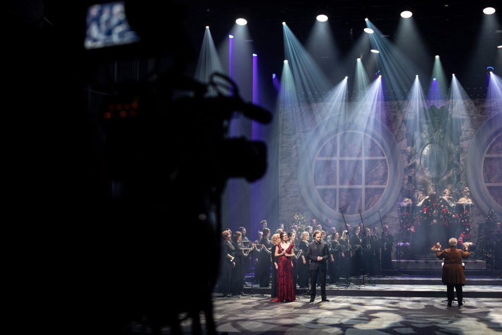 Na scenie stoi dwójka solistów, kobieta w czerwonej sukni i mężczyzna w czarnym garniturze. Za nimi chór opery w czarnych strojach. Na środku stoi dyrygent i kierownik chóru Prof. Violetta Bielecka. Na środku duży kominek w którym pali się ogień. Po lewej stronie widać cień kamery.