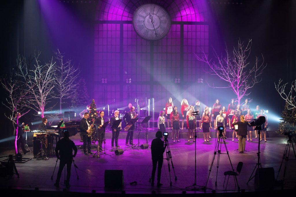 Scena oświetlona fioletowym światłem. Na środku stoi chór dziecięcy ubrany w swetry z motywami świątecznymi. Przed nimi stoi kierownik chóru. Po lewej stronie stoi czterech mężczyzn. Trzech gra na saksofonach, jeden na trąbce. Z przodu dwie osoby przy statywach z aparatami. Po obydwu stronach szare drzewa bez liści.
