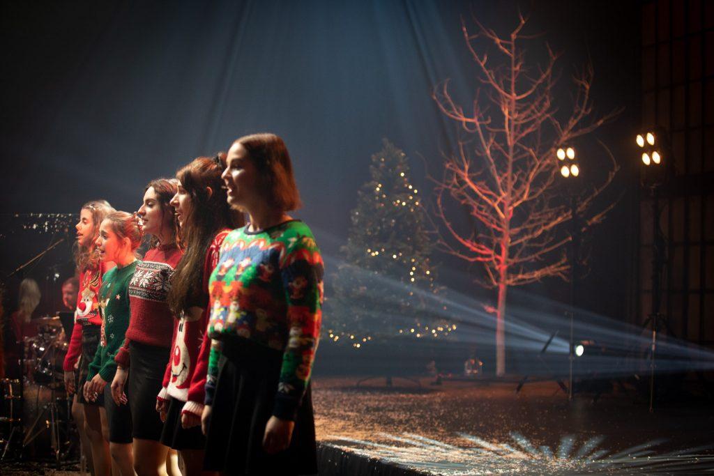 W rzędzie stoi kilka dziewcząt z chóru dziecięcego. Wszystkie ubrane w swetry z motywami świątecznymi. Na scenie za nimi stoi choinka ze światełkami, obok szare drzewo bez liści, podświetlone na czerwono.
