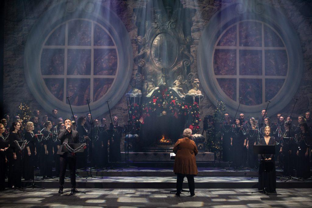 Na środku sceny stoi dyrygent i kierownik chóru Prof. Violetta Bielecka. Po obydwu stronach stoją soliści, po prawej stronie kobieta w czarnej, długiej sukni, po lewej stronie mężczyzna w garniturze. Za nimi stoi chór opery. Na środku stoi duży kominek ozdobiony bombkami w którym pali się ogień.
