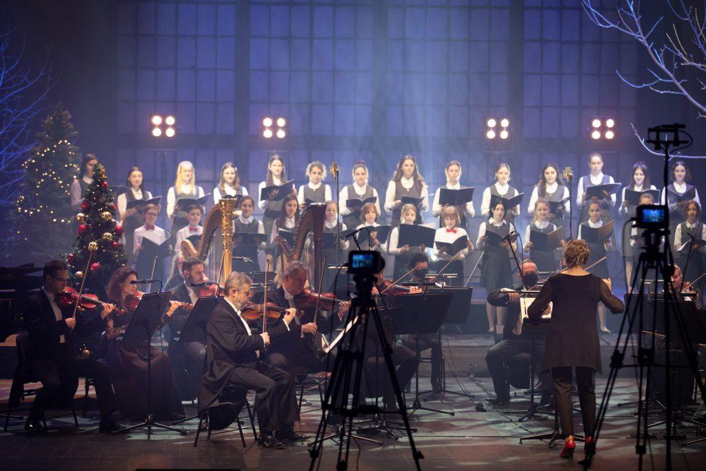 Na scenie gra sekcja smyczkowa Orkiestry Opery i Filharmonii Podlaskiej. Za nimi stoi chór dziecięcy. Wszyscy trzymają otwarte nuty. Z przodu na statywach aparaty.