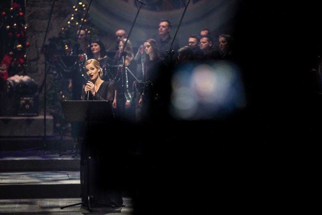 Po lewej stronie śpiewa solistka w długiej, czarnej sukni. Za nią stoi część chóru opery.