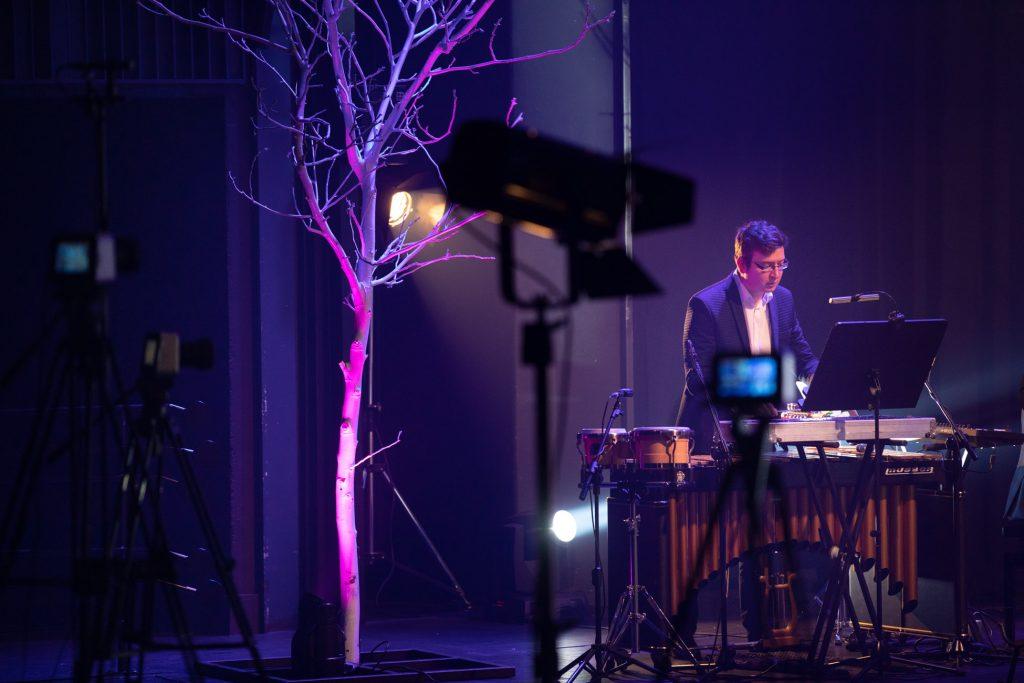 Scena oświetlona na niebiesko. Mężczyzna w garniturze gra na dzwonkach. Po lewej stronie szare drzewo bez liści podświetlone na biało. Obok kilka statywów z aparatami i reflektorami.