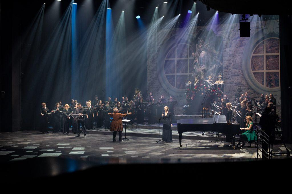 Na scenie trwa koncert ''Siła serc''. Na środku stoi solistka w czarnej, długiej sukni. Po prawej stronie przy fortepianie siedzi kobieta w zielonej sukni. Po lewej stronie stoi solista w garniturze. Z tyłu , z obydwu stron stoi chór opery ubrany na czarno. Na środku przed pulpitem, z rękoma uniesionymi w bok , stoi dyrygent i kierownik chóru.