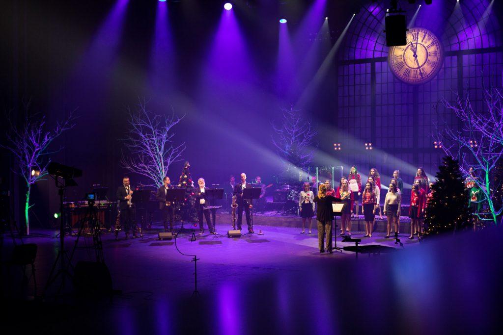 Scena oświetlona niebiesko-fioletowym światłem. Na środku stoi chór dziecięcy ubrany w swetry z motywami świątecznymi. Przed nimi stoi kierownik chóru. Po lewej stronie stoi czterech mężczyzn przy pulpitach do nut. Wokół szare drzewa bez liści podświetlone na zielono. Z tyłu wisi duży jasny zegar.