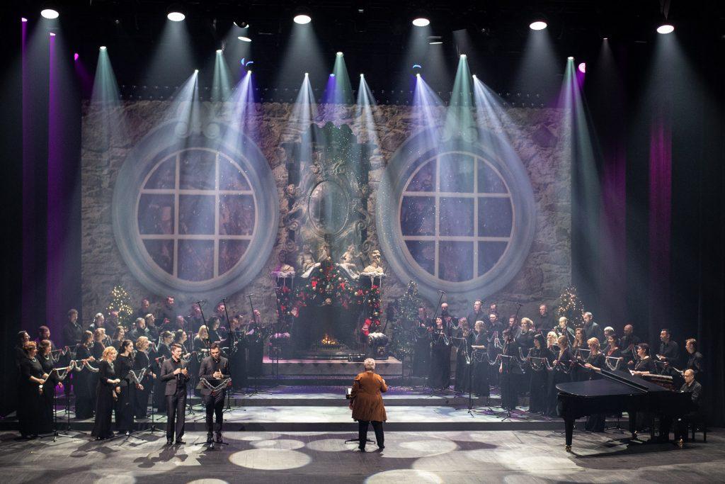 Na scenie Chór Opery i Filharmonii Podlaskiej. Po prawej stronie przy fortepianie siedzi mężczyzna. Po lewej stronie stoi dwóch solistów. Na środku stoi dyrygent i kierownik chóru. Na końcu sceny widoczny duży kominek ozdobiony bombkami w którym pali się ogień.