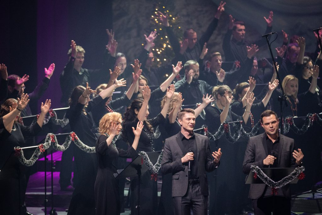 Dwóch solistów w czarnych garniturach stoi z mikrofonami. Za nimi chór opery. Wszyscy mają uniesione ręce do góry.