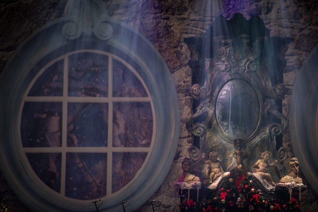 Na zdjęciu zbliżenie na element scenografii przedstawiający namalowane okrągłe okno, obok ozdobne lustro.