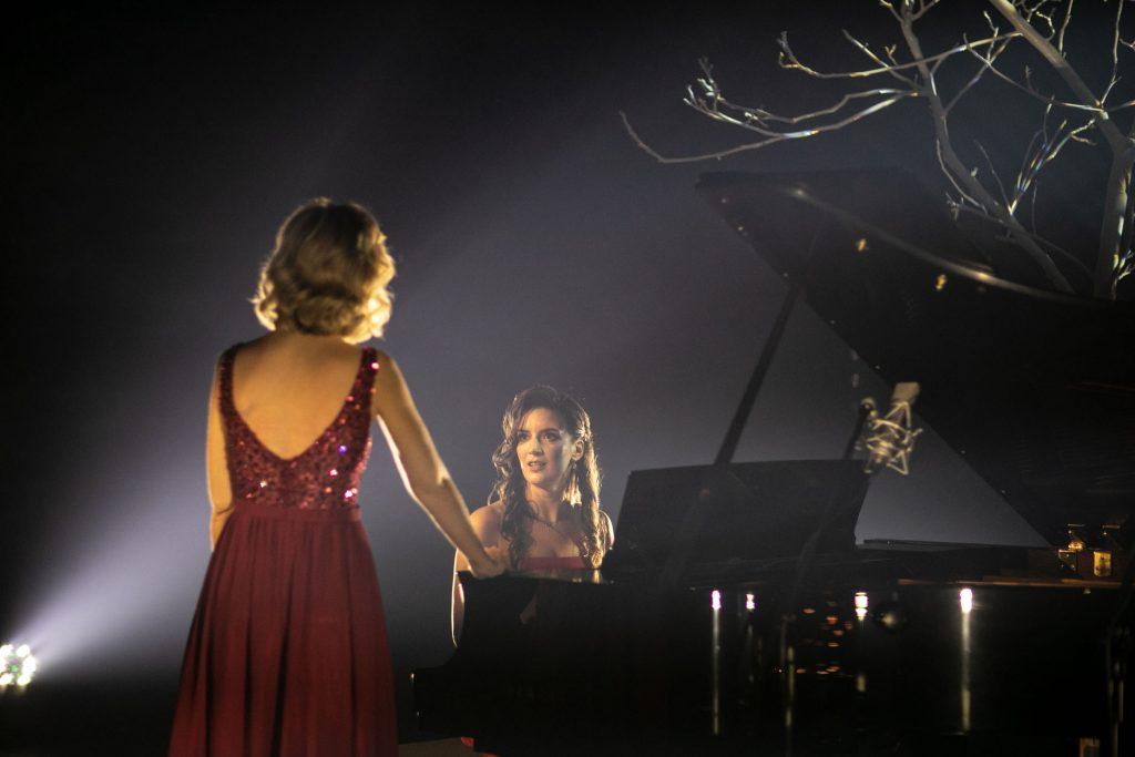 Scena w półmroku. Kobieta siedząca przy fortepianie patrzy w kierunku kobiety w bordowej sukni , stojącej przed nią.