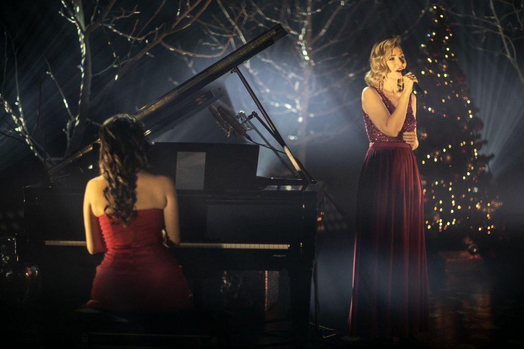 Na scenie dwie kobiety. Jedna, w czerwonej sukni siedzi przy fortepianie. Druga w sukni bordowej stoi z mikrofonem. W oddali drzewa bez liści oświetlone smugami białego światła. Po prawej stronie choinka z bombkami.