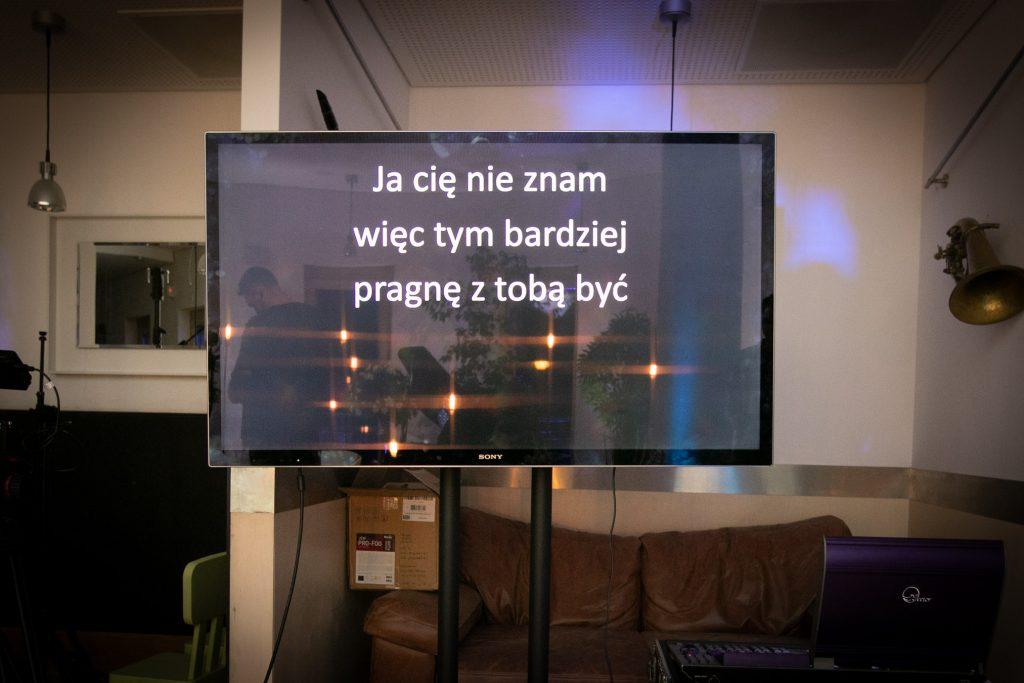 Na środku stoi telewizor, na nim wyświetla się napis '' Ja cię nie znam więc tym bardziej pragnę z tobą być''. Za nim stoi brązowa sofa.