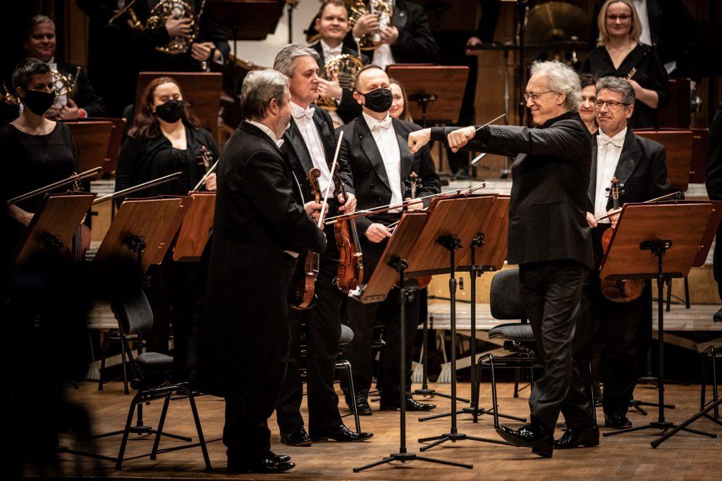 Scena sali Opery i Filharmonii Podlaskiej przy ulicy Podleśnej. Na środku mężczyzna stojący bokiem, trzyma ręce wyciągnięte przed siebie. W lewej dłoni trzyma batutę. Przed nim stoi przy pulpitach kilka kobiet i mężczyzn z sekcji smyczkowej. Dalej widoczna grupa dęta orkiestry.