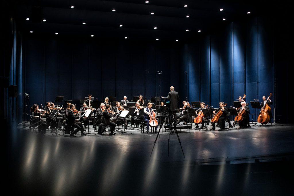 Scena słabo oświetlona. Na środku siedzi sekcja smyczkowa orkiestry. Za nią siedzą muzycy z instrumentami dętymi. Na środku, na podeście stoi dyrygent.