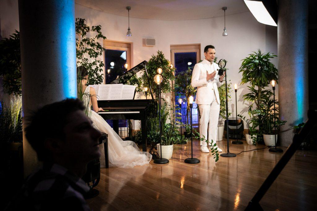 Przy mikrofonie na statywie stoi mężczyzna w białym garniturze. Obok , przy pianinie siedzi kobieta w długiej, białej sukni. Wokół nich stoją kwiaty w donicach.