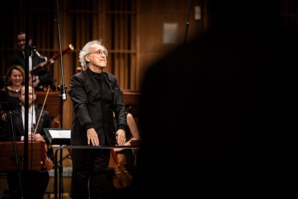 Mężczyzna w czarnym kostiumie stoi przodem na podeście. W lewej ręce trzyma batutę. Za nim widoczna część orkiestry Opery i Filharmonii Podlaskiej.