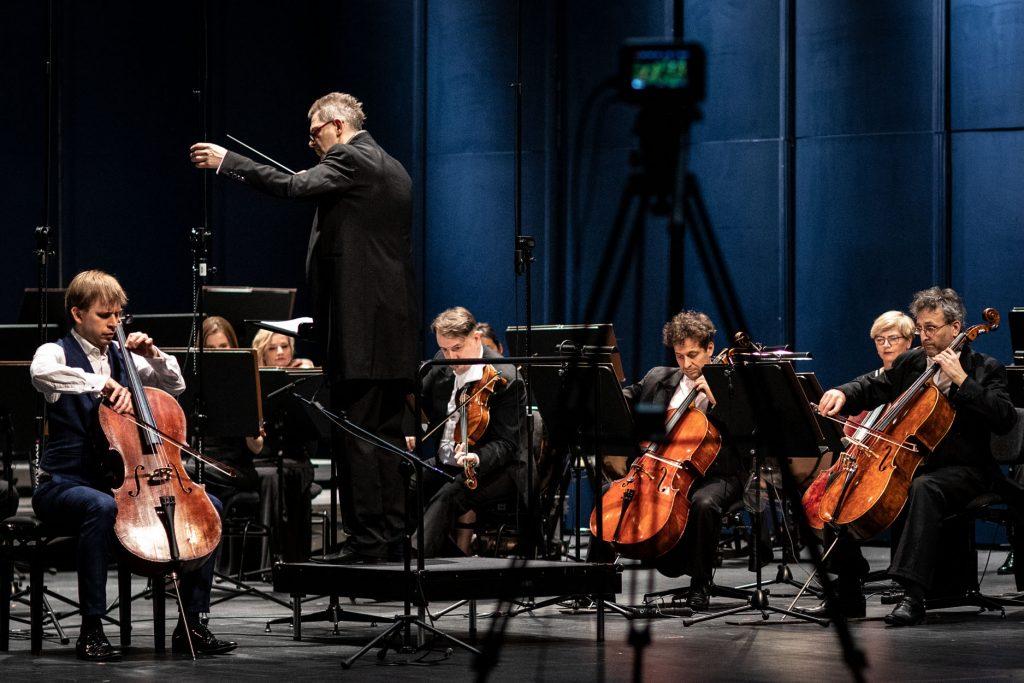 Na zdjęciu widoczna część orkiestry z sekcji smyczkowej podczas koncertu. Z przodu , na podeście stoi dyrygent.