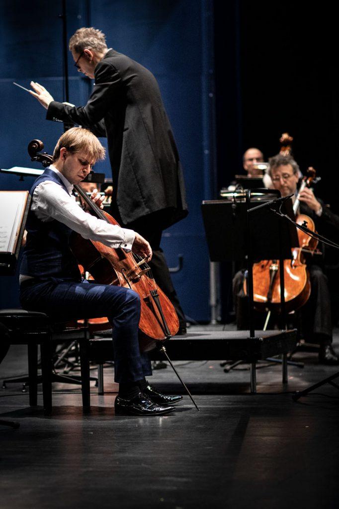 Na zdjęciu widać dwóch mężczyzn grających na wiolonczelach. Pomiędzy nimi stoi dyrygent.