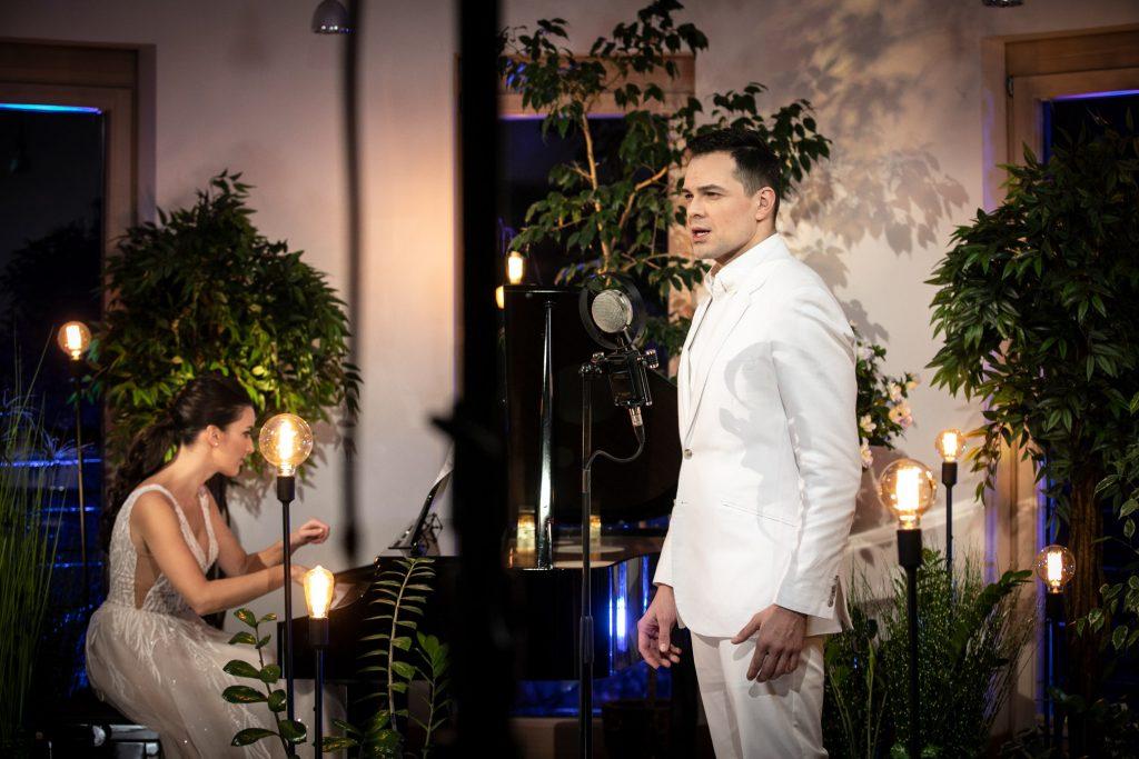 Mężczyzna w białym garniturze stoi przed mikrofonem. Dalej, przy pianinie siedzi kobieta w jasnej sukni. Dookoła nich stoją wąskie, wysokie lampki oraz kwiaty w donicach.