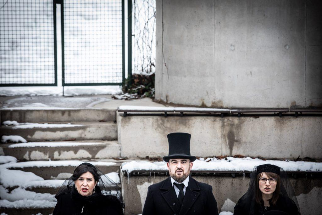 Amfiteatr opery. Zbliżenie na twarze trzech osób, mężczyzny w kapeluszu i dwóch kobiet stojących obok siebie.