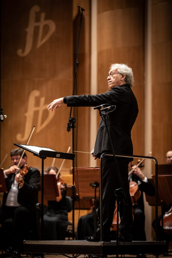 Zbliżenie na podest na którym stoi dyrygent. Dalej widoczna część sekcji smyczkowej podczas wykonywania utworu.