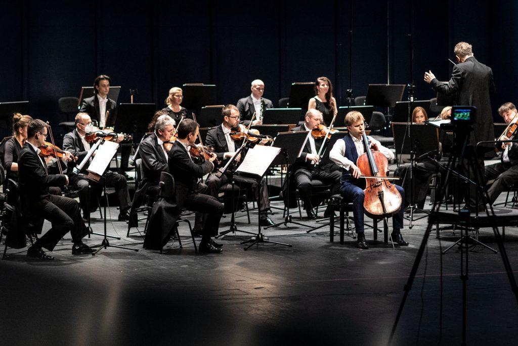 Na scenie gra część orkiestry z sekcji smyczkowej. Za nimi siedzi kilku muzyków z sekcji dętej. Z przodu stoi dyrygent z rękami uniesionymi do góry. Po prawej stronie stoi aparat na wysokim statywie.
