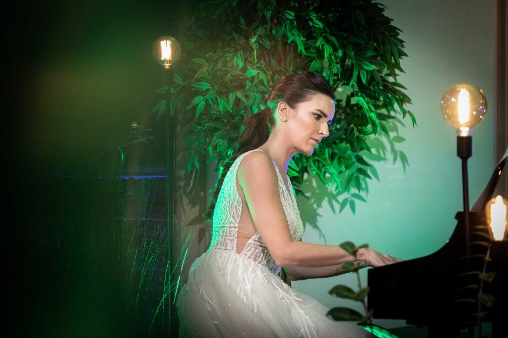 Kobieta w jasnej sukni siedzi przy pianinie. Wokół niej stoją lampi na długich, czarnych statywach. Za nią stoi drzewo pełne liści.