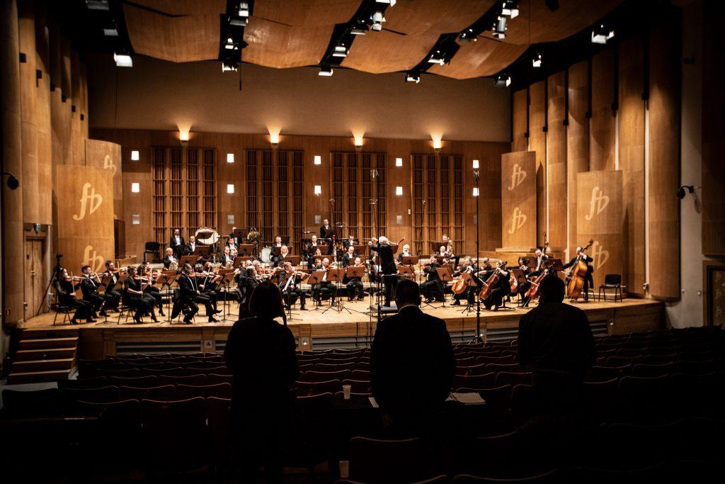 Scena sali koncertowej przy ulicy Podleśnej. Zdjęcie zrobione z końca widowni. Na scenie siedzi Zespół Kameralny Ars Iuvenum. Przed nimi na podeście stoi dyrygent. Na widowni, w półmroku stoi kilka osób.